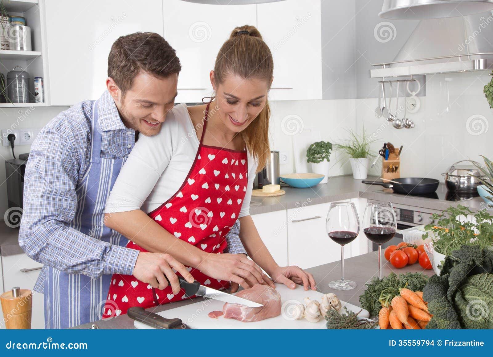 在一起烹调在厨房里的爱的夫妇和获得乐趣
