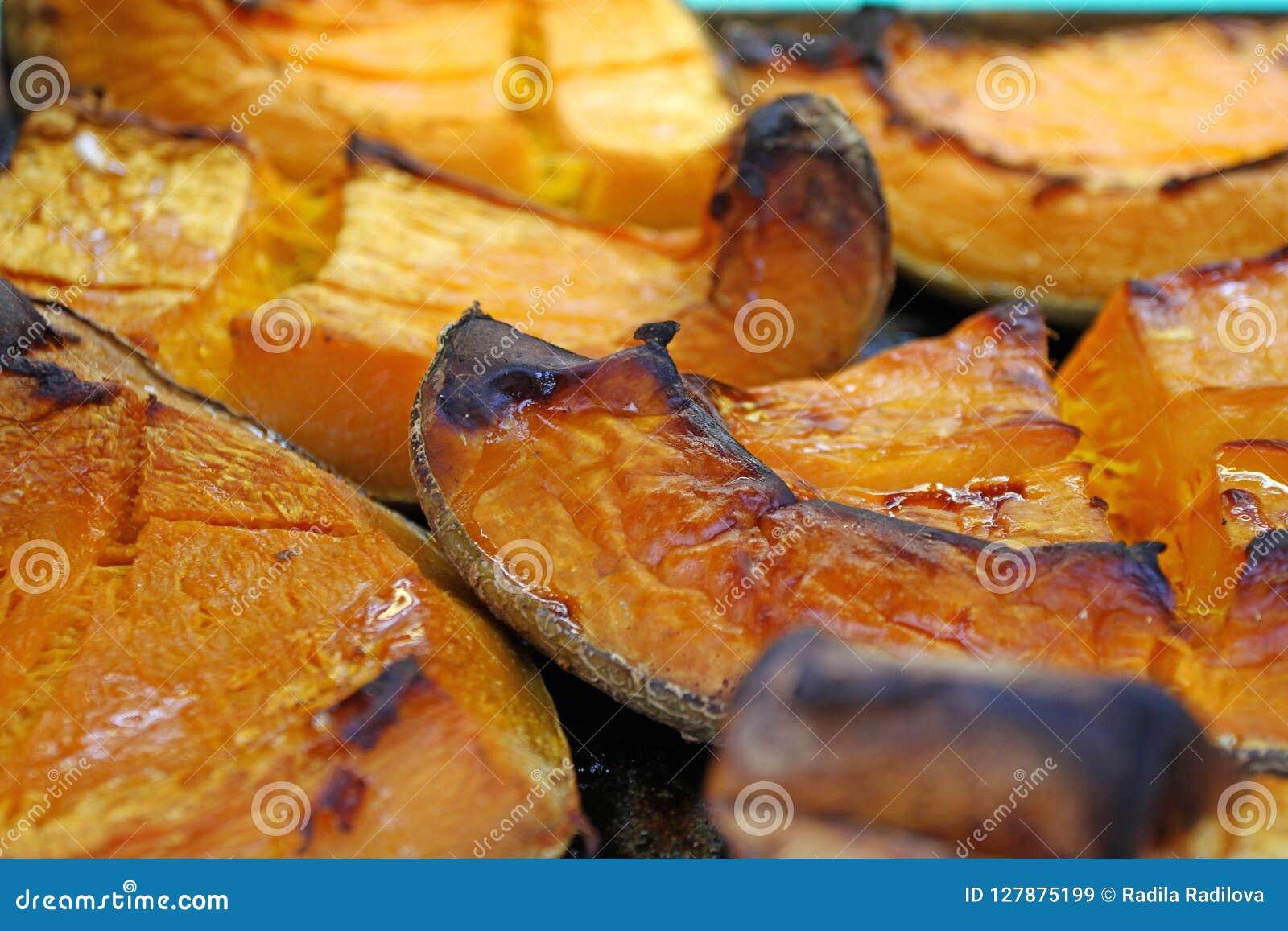 在万圣夜假日烘烤的有机南瓜切片 五颜六色的被烘烤的南瓜背景 南瓜纹理样式 甜点烤pumpki