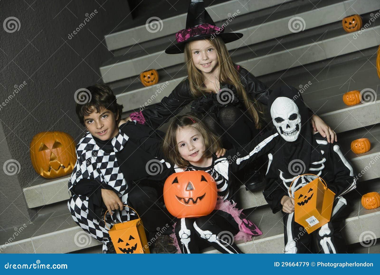 在万圣夜服装的孩子坐台阶