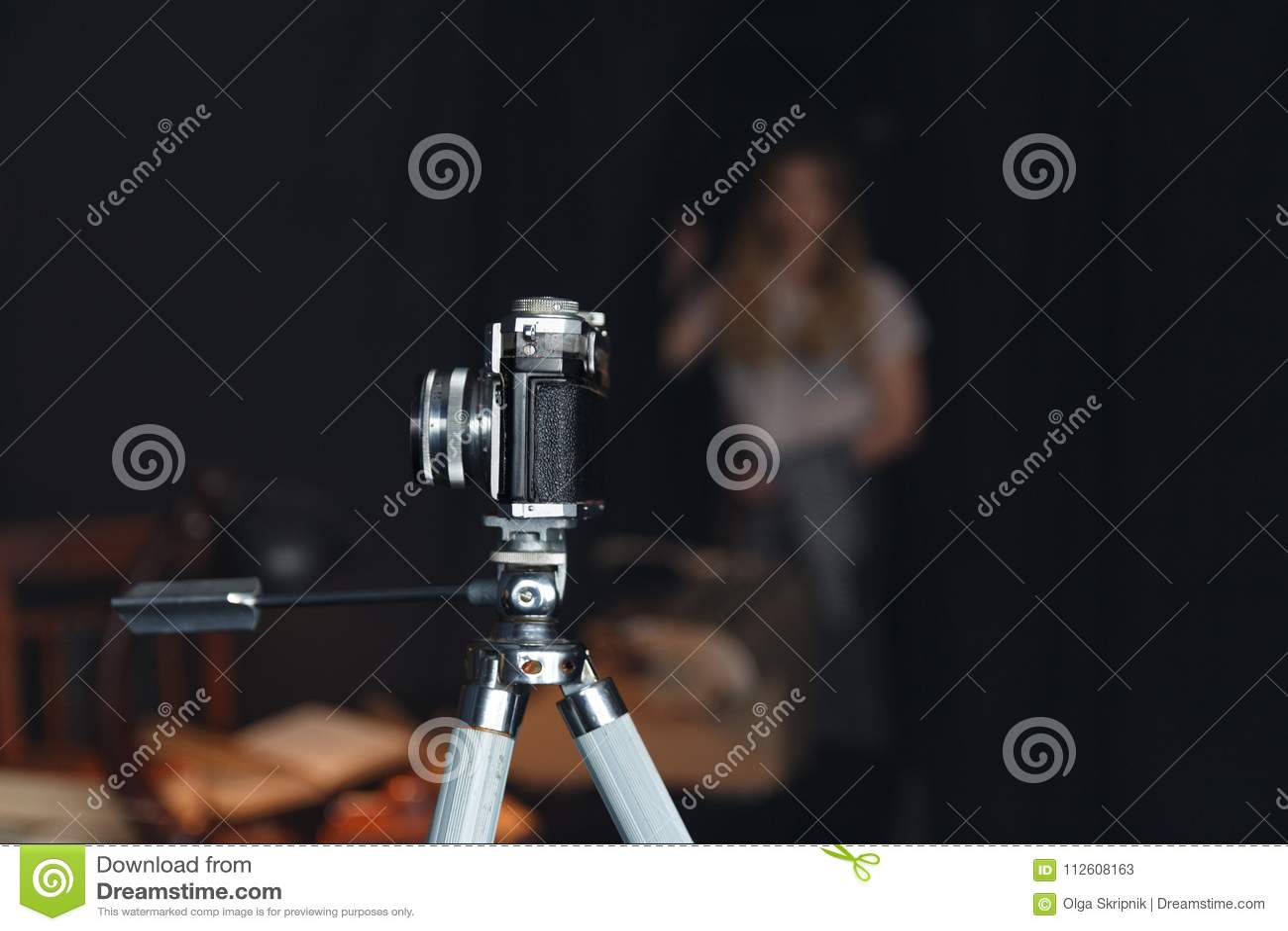 在三脚架的老照相机在屋子里站立