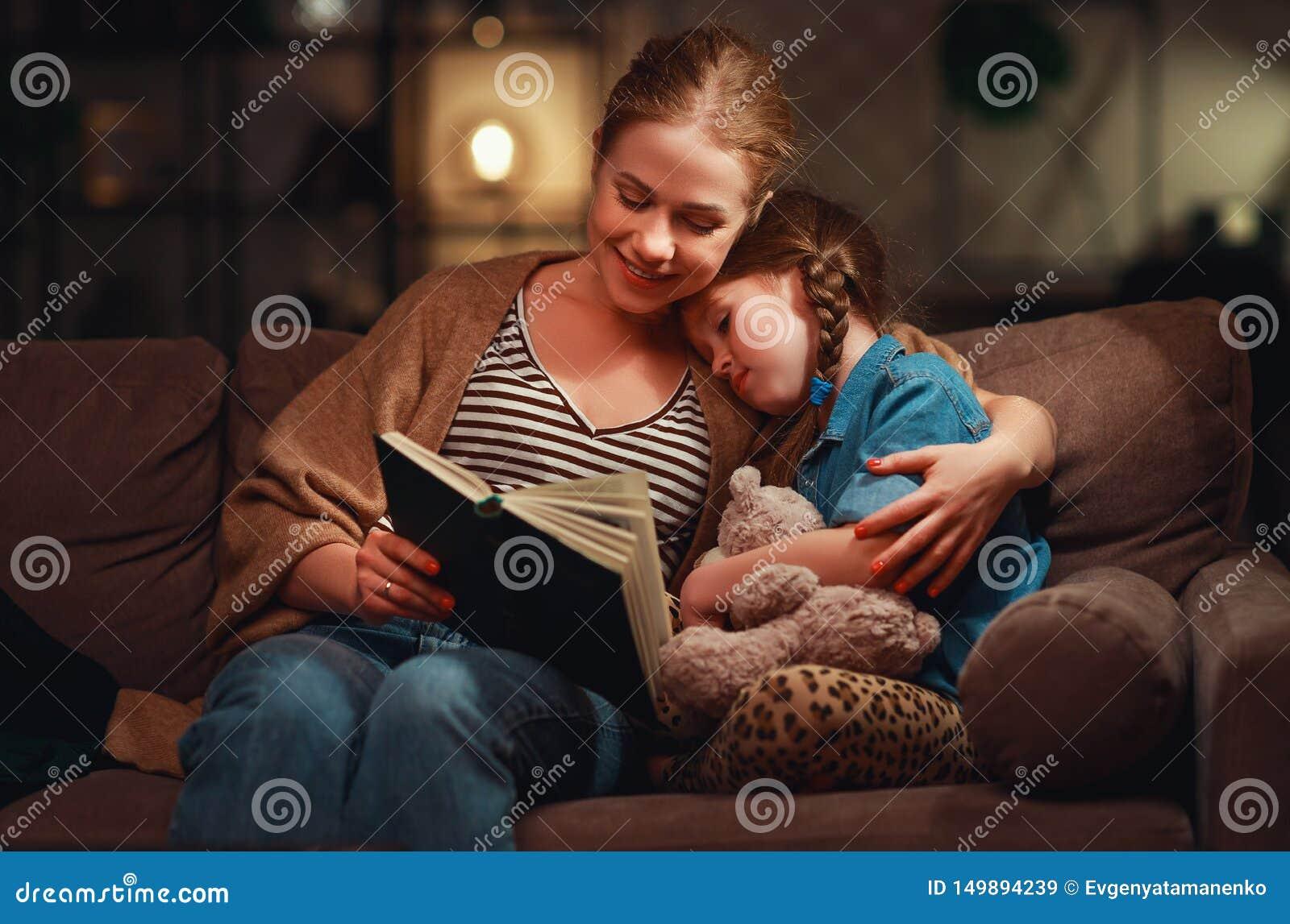 在上床的母亲前的家庭读对她的儿童女儿书在一盏灯附近在晚上