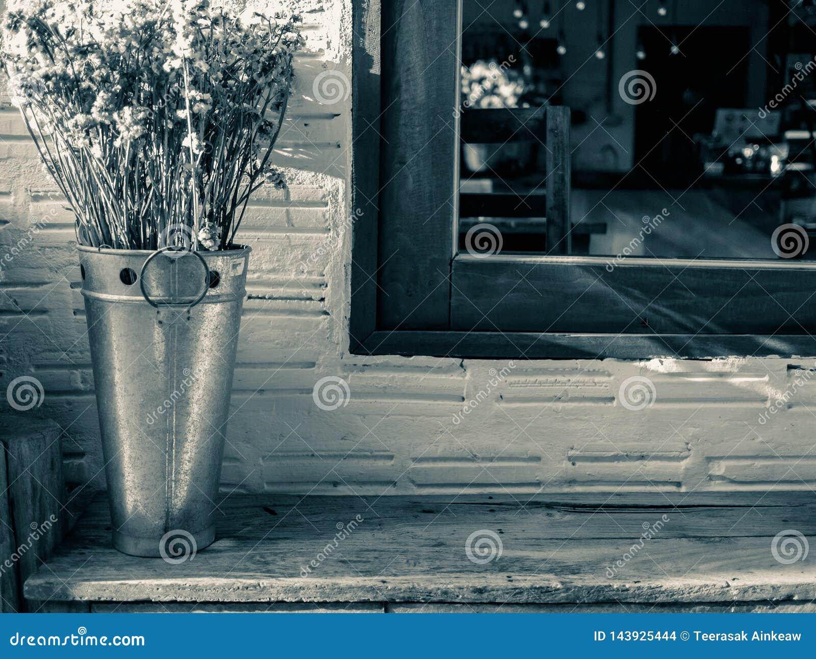 在不锈钢坦克的干花在临近与阳光的木椅子窗口在晚上 背景概念