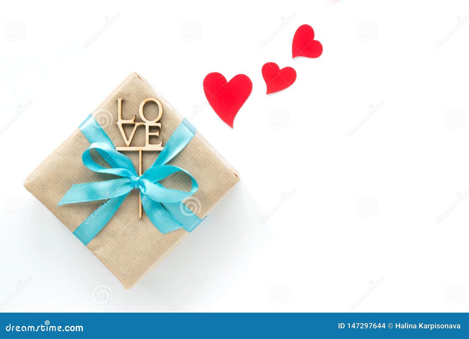 在与浅兰的丝带的在白色背景的包装纸和红心包裹的礼物盒 r Copyspace