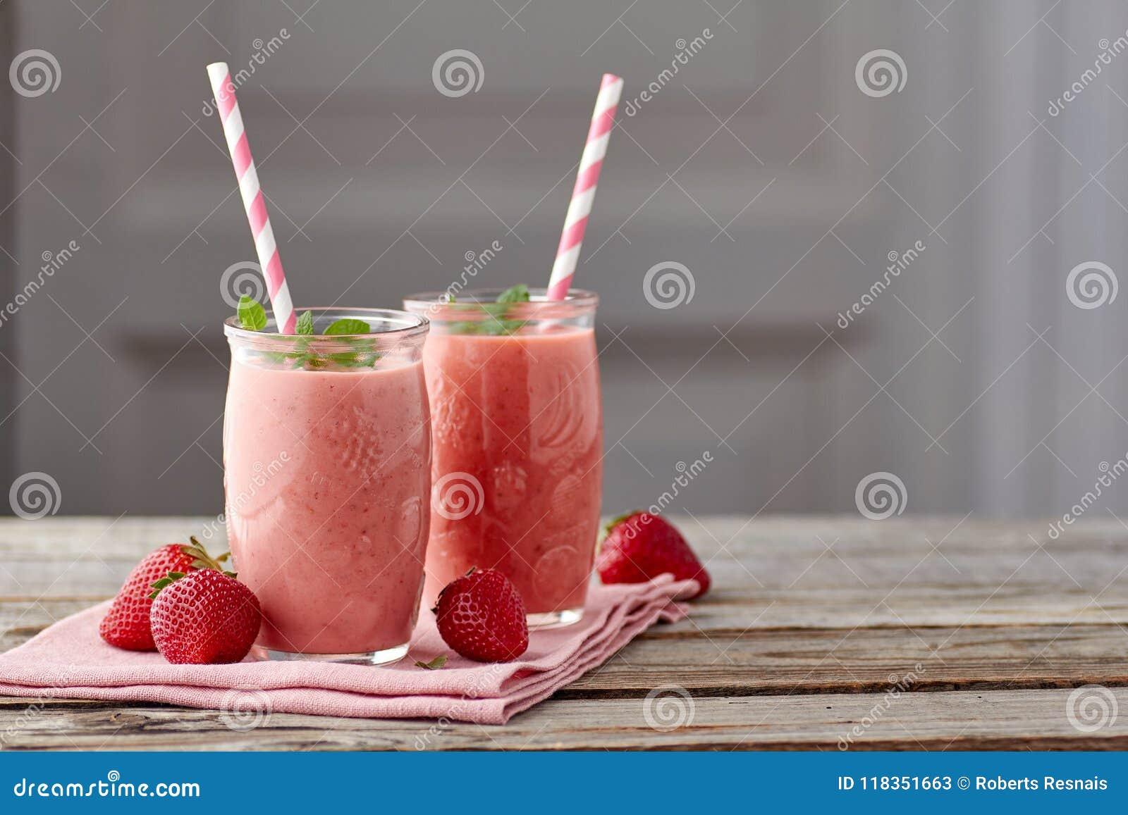 在两个瓶子的酸奶和草莓圆滑的人有在木桌上的吸管的