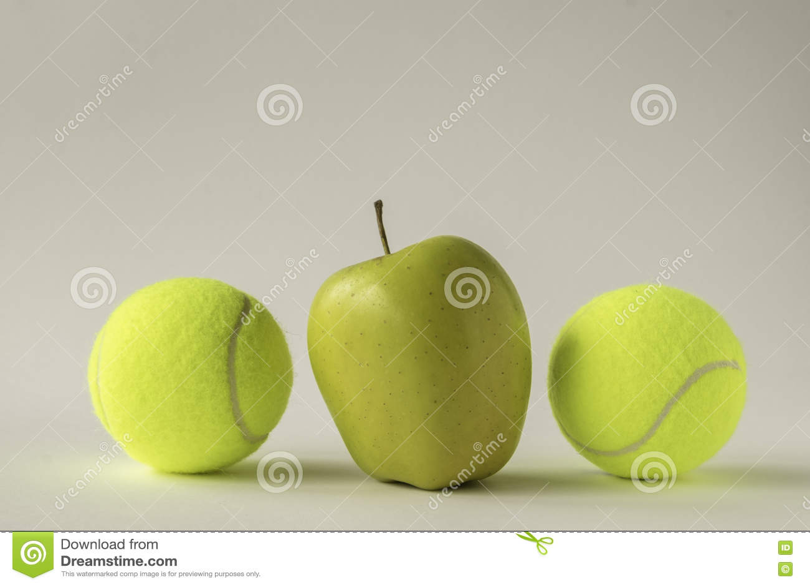在两网球之间的黄色苹果