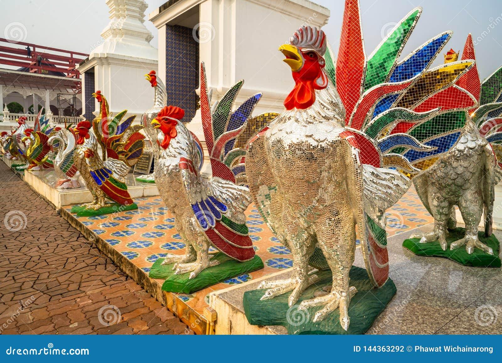 在主闸前面的五颜六色的雄鸡雕象在佛教寺庙在泰国
