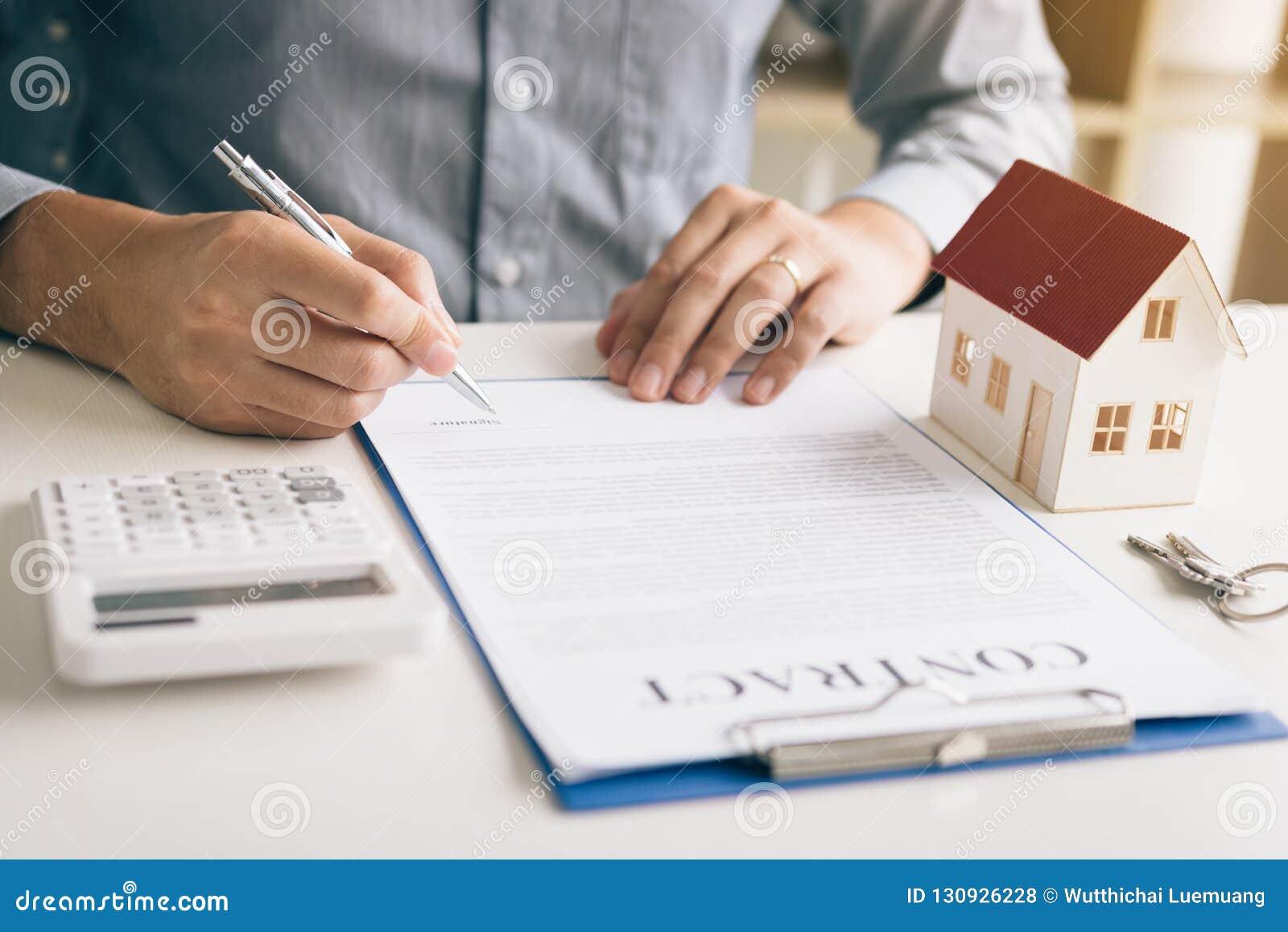 在书桌上的新的购房者签署的合同在办公室屋子里