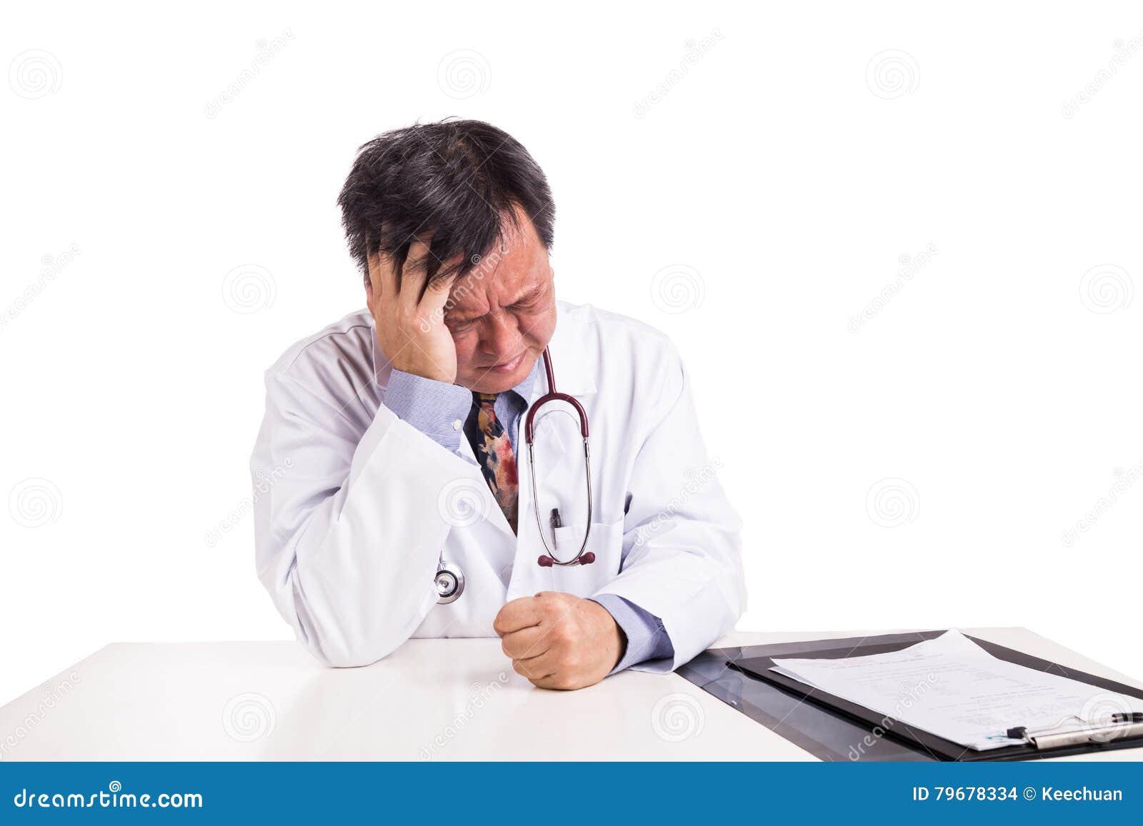 在书桌后安装的沮丧的哀伤的成熟的亚裔医生