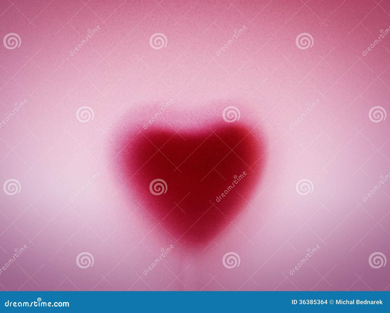 在乳状毛玻璃后的心脏形状。爱,浪漫背景