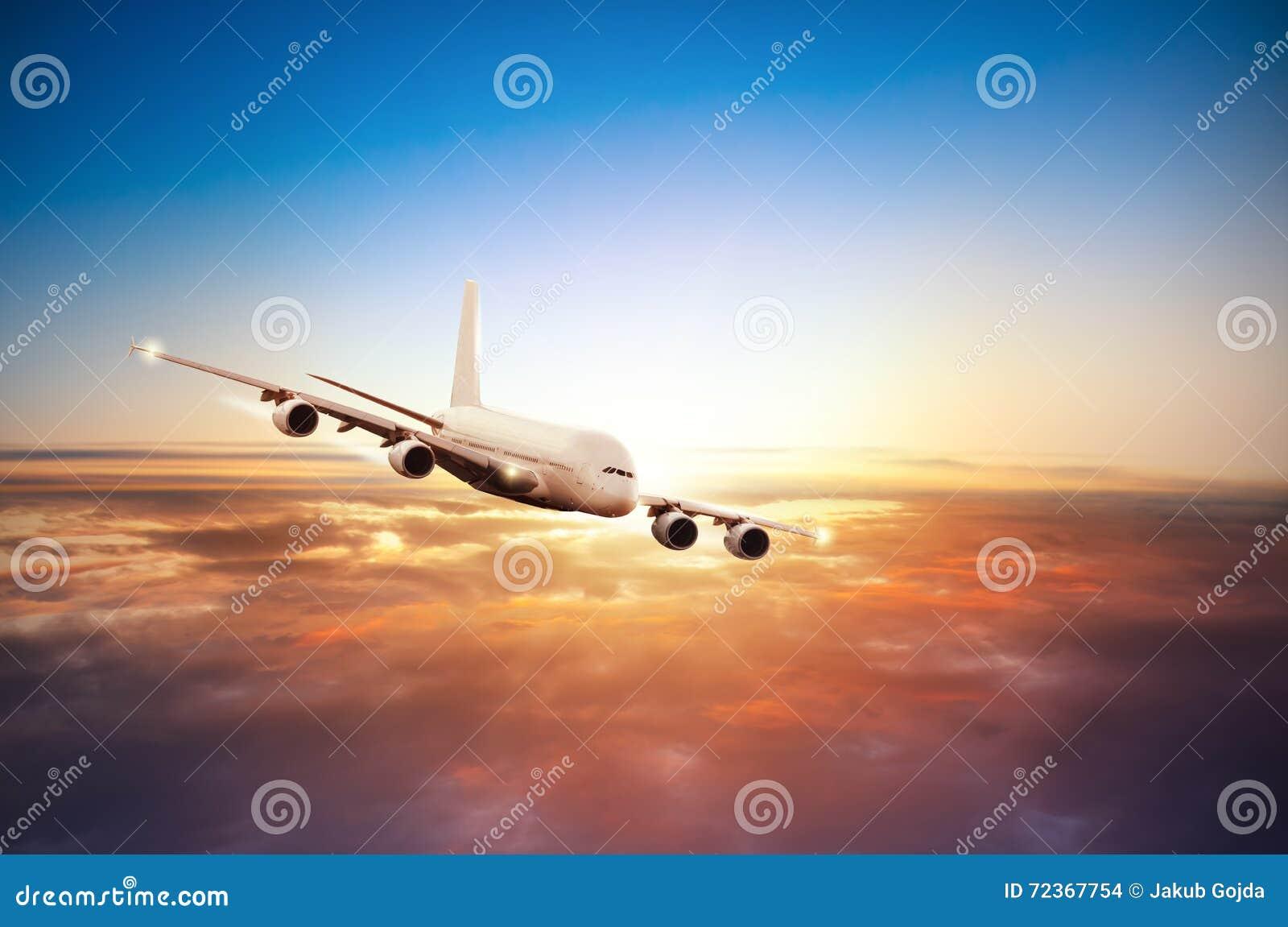 在云彩上的飞机飞行在剧烈的日落