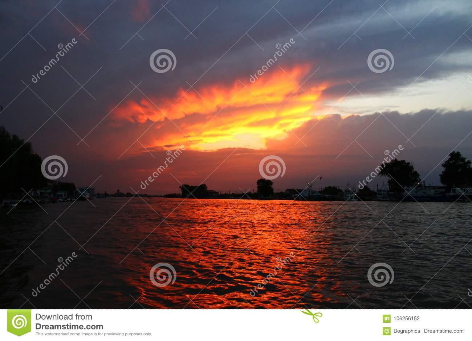 在云彩之间的惊人的橙色日落在水