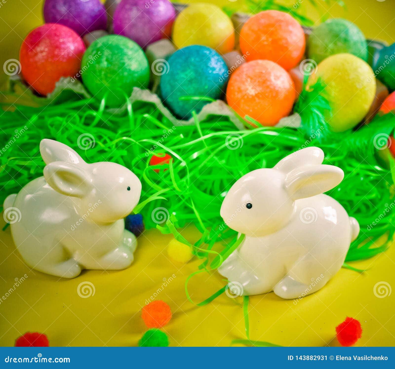 在五颜六色的明亮的鸡蛋附近的两只白色porctlain兔子