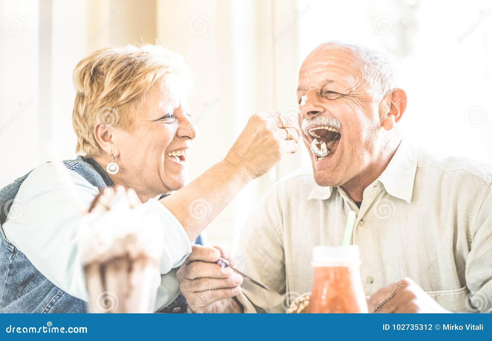在享用生物冰淇凌杯子的爱的愉快的退休的资深夫妇