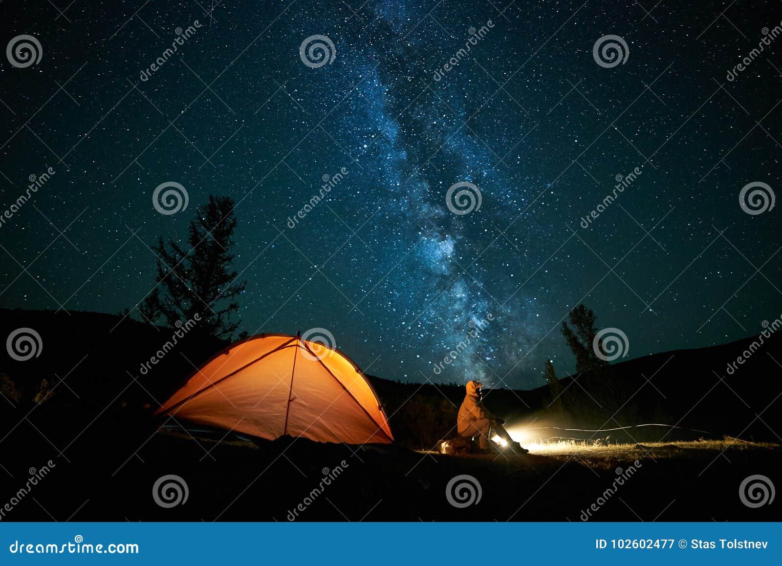 在他的阵营帐篷附近的游人在晚上