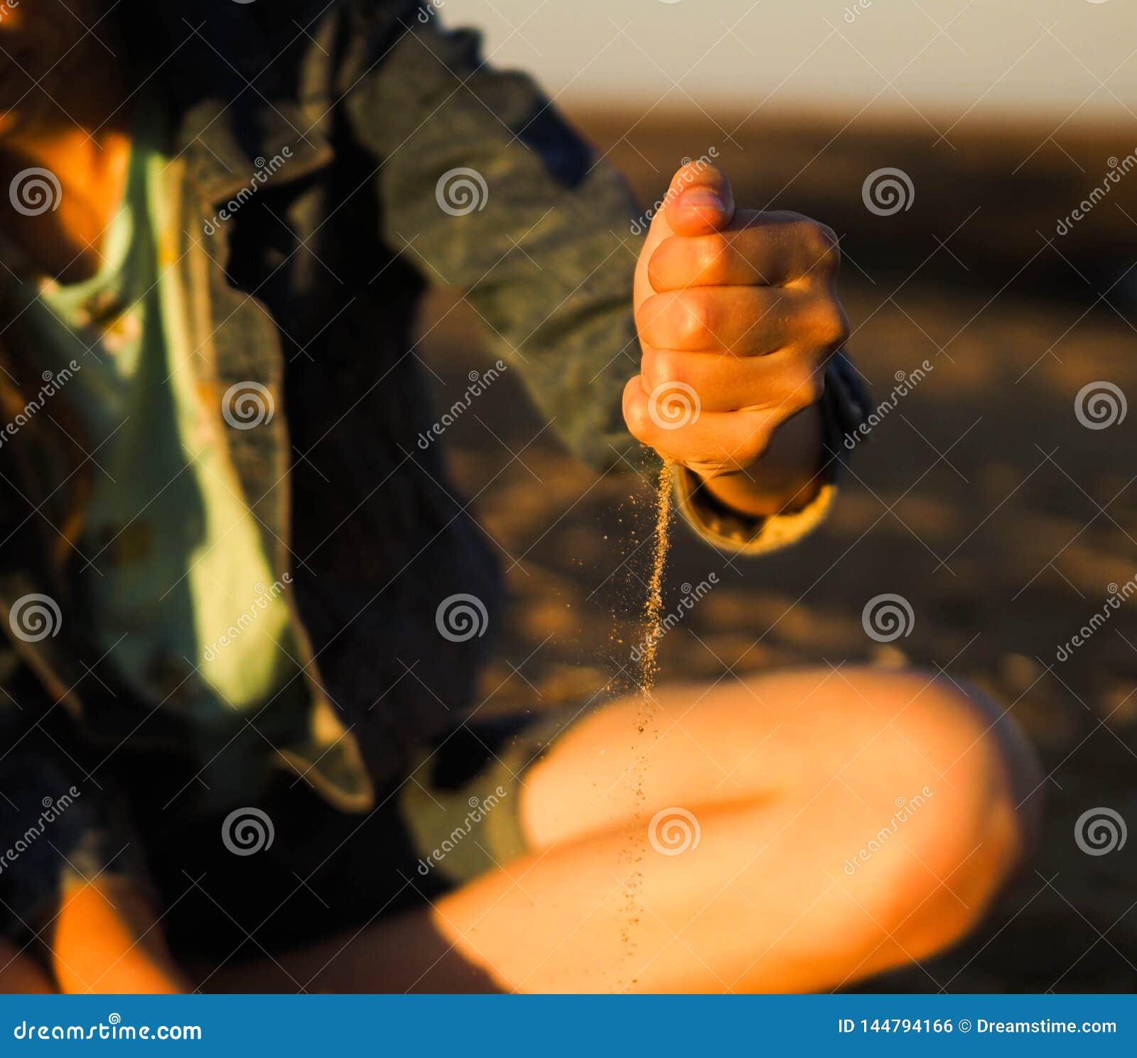 在他的handsn的女孩沙子