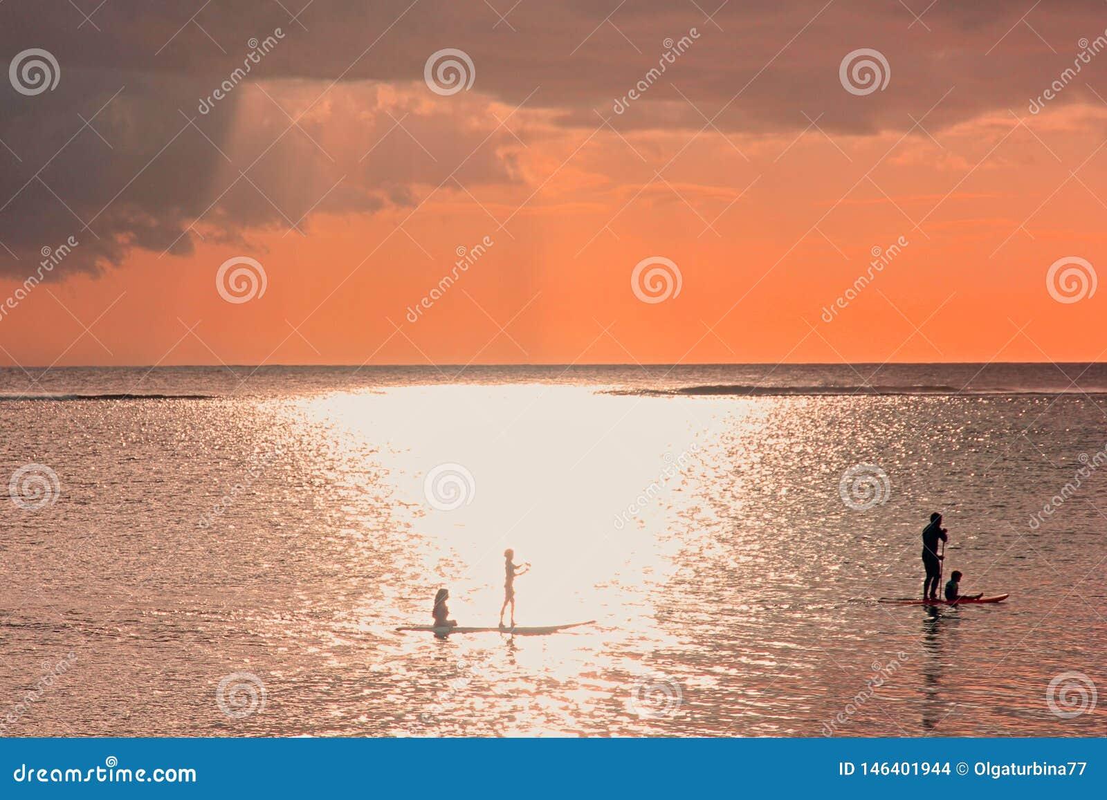 在以后的雷暴背景的日落场面 在日落的家庭剪影在海洋 有三个孩子的一个父亲用浆划