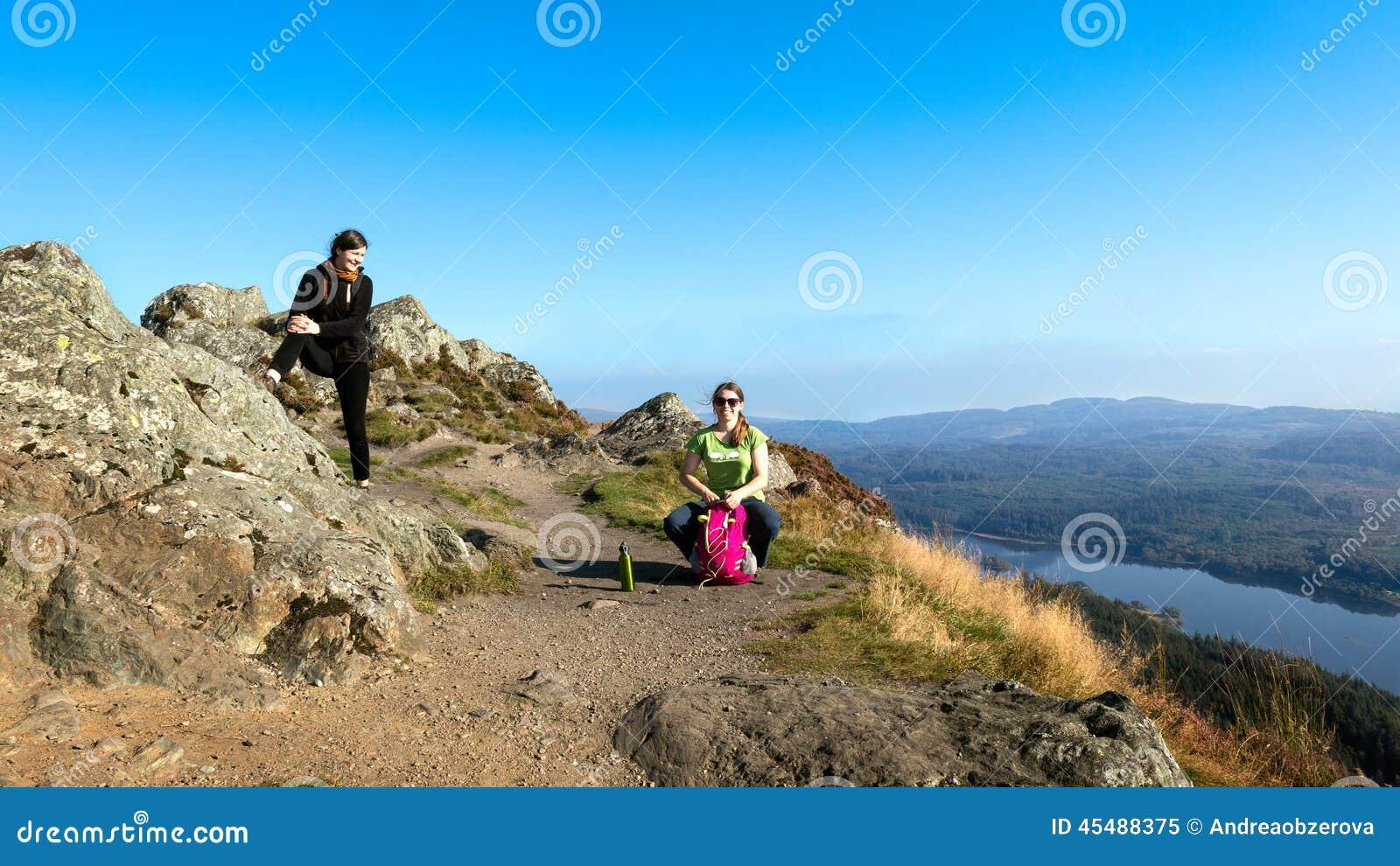 在休假和享受谷视图的山顶部的女性远足者