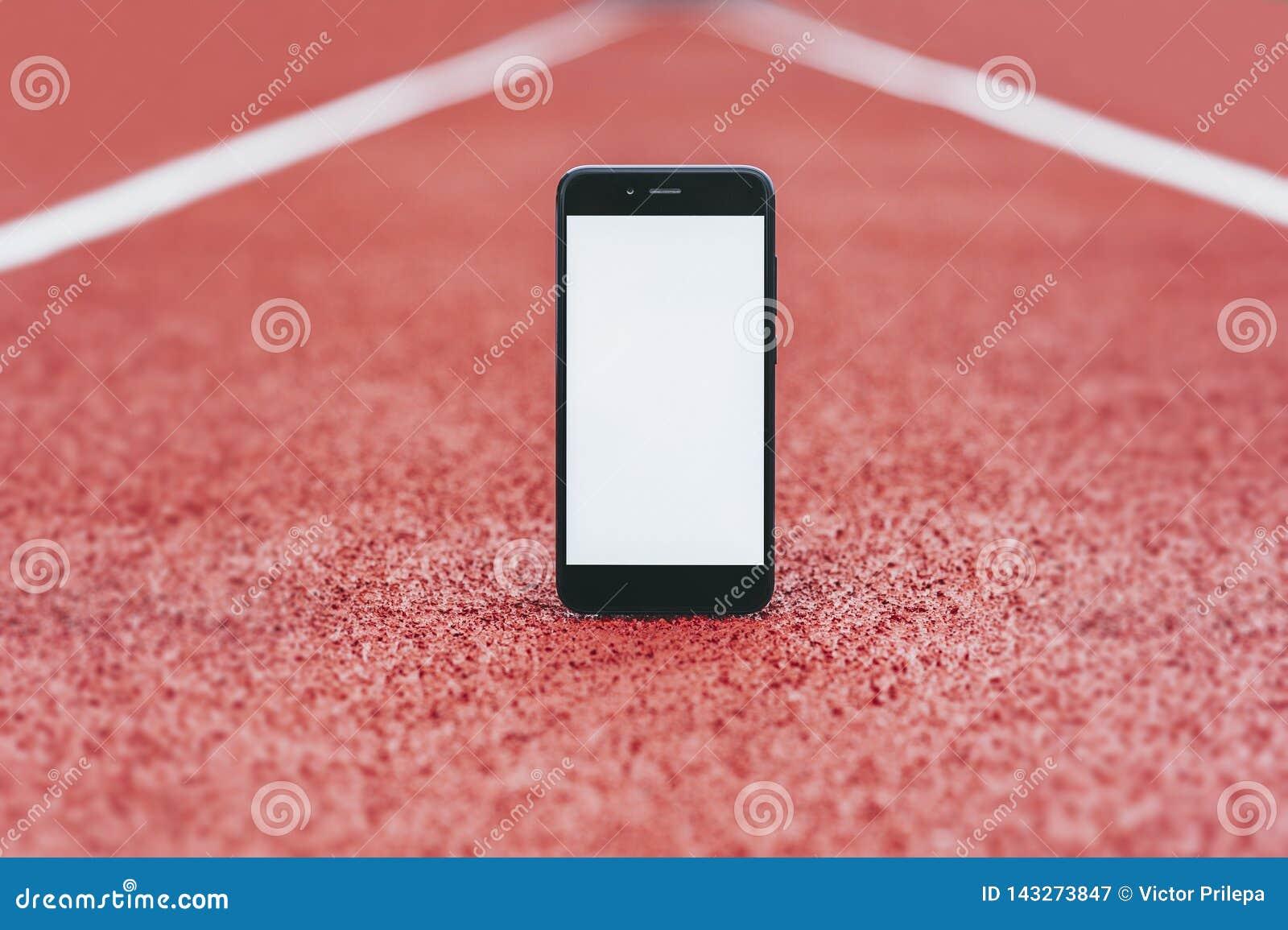在体育场的假装智能手机跑的 在体育题目的概念
