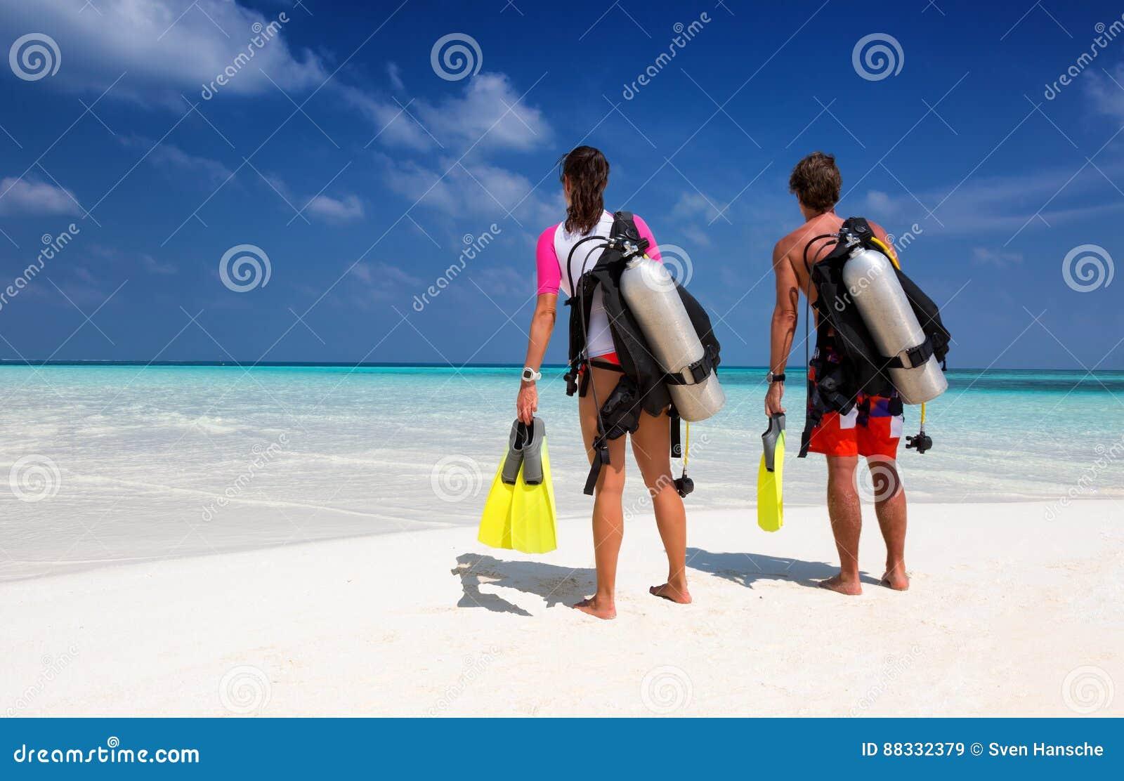 在佩戴水肺的潜水齿轮的年轻夫妇