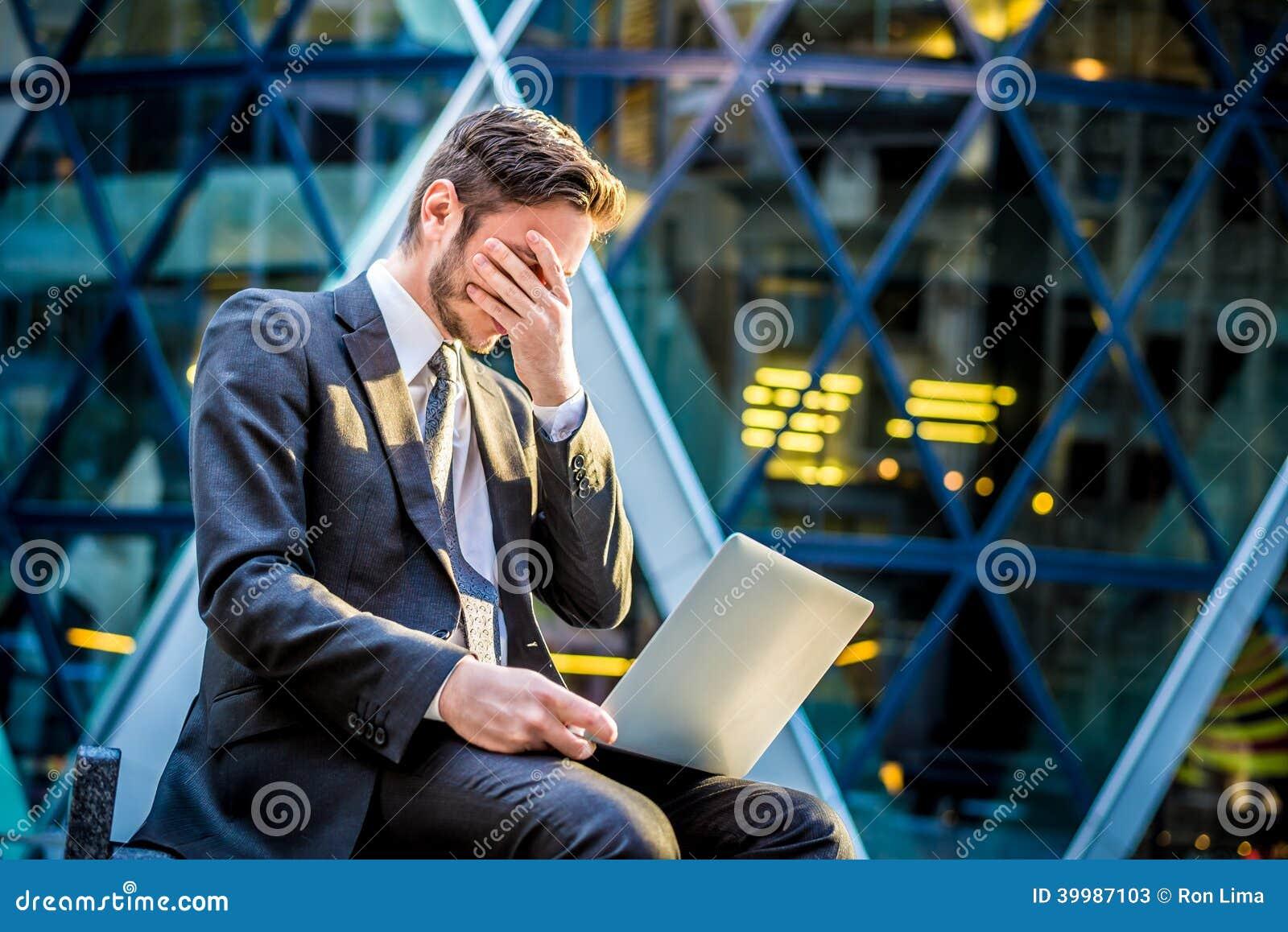 在便携式计算机上的沮丧的商人