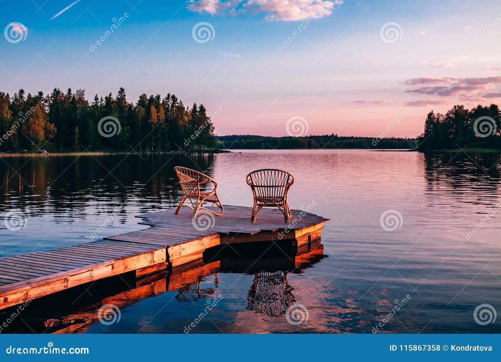 在俯视湖的木码头的两把木椅子在日落
