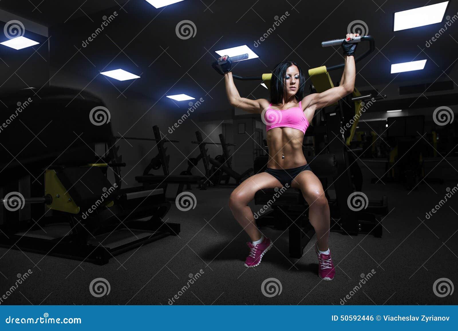 在健身房的性感的运动员妇女推力
