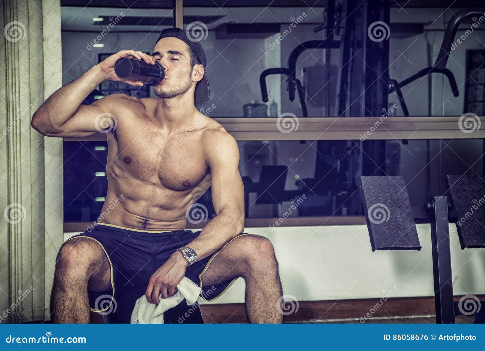 在健身房的赤裸上身的年轻人饮用的蛋白质震动