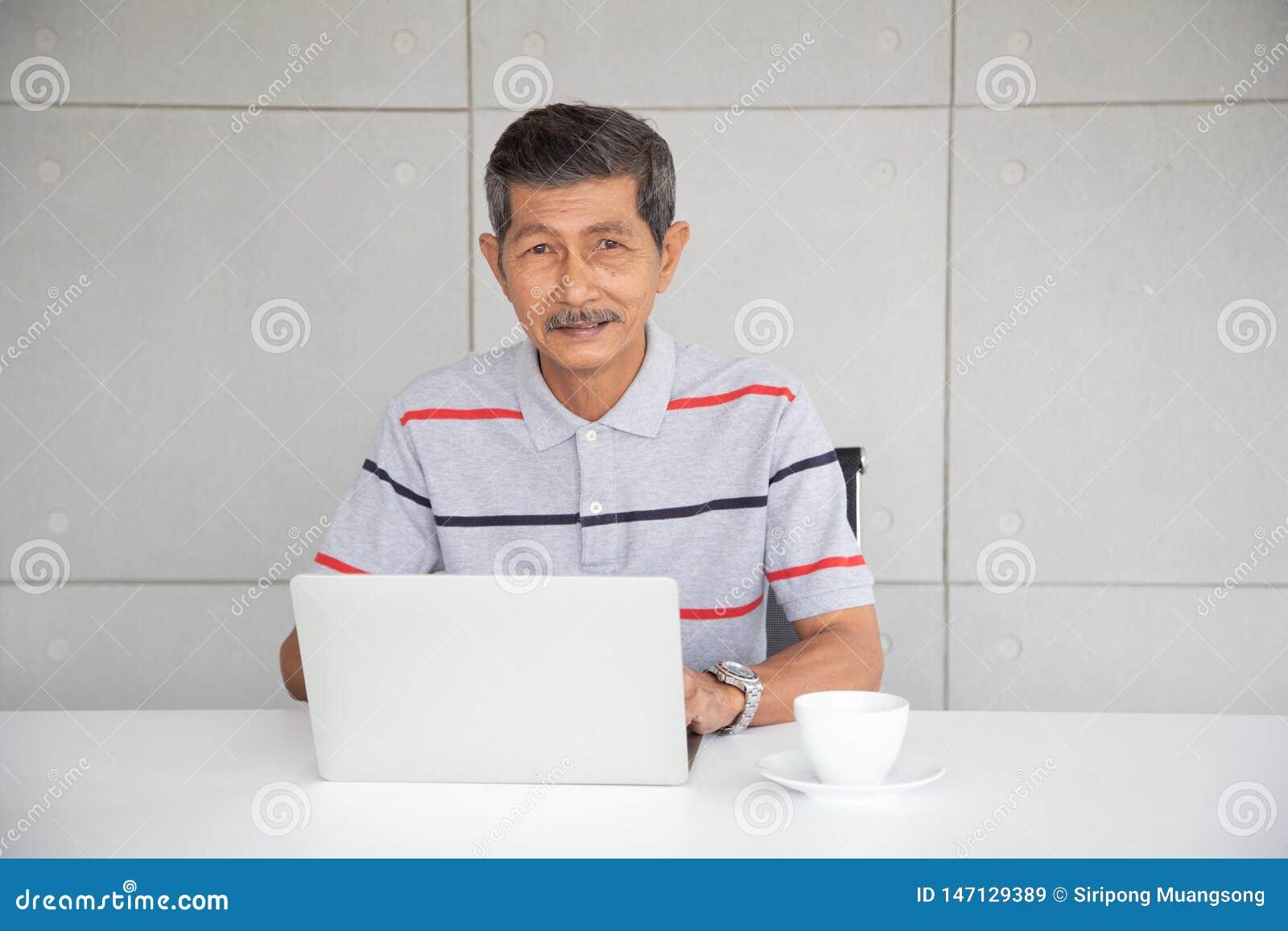 在偶然工作的资深亚洲商人在用途膝上型计算机旁边