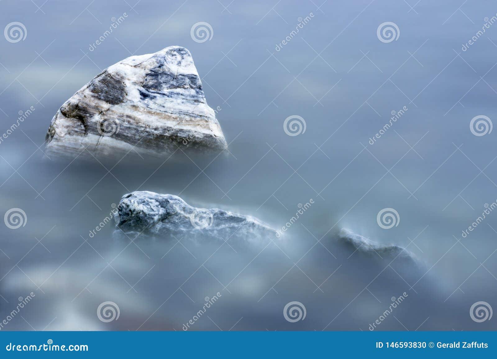 在光滑的大海的镶边岩石