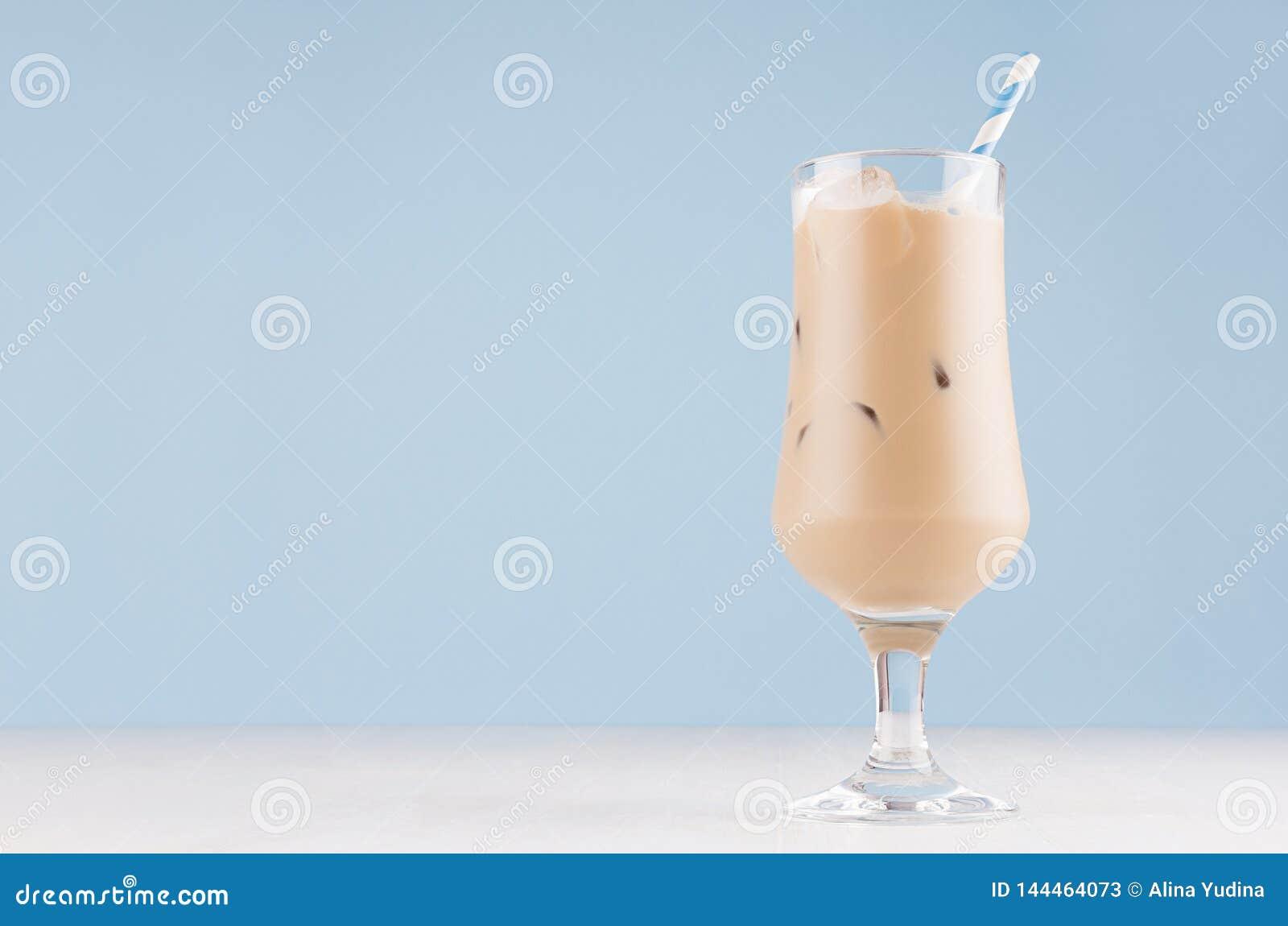 在典雅的透明玻璃的乳脂状的冷的新鲜的饮料与冰块和镶边秸杆在现代浅兰的内部
