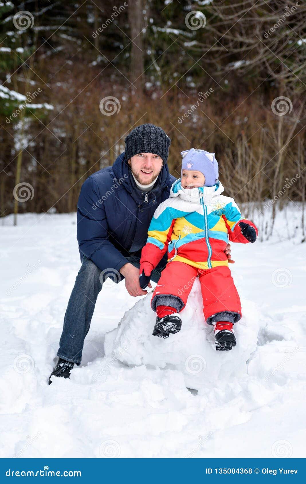在冬天森林爸爸妈妈和孩子的家庭步行