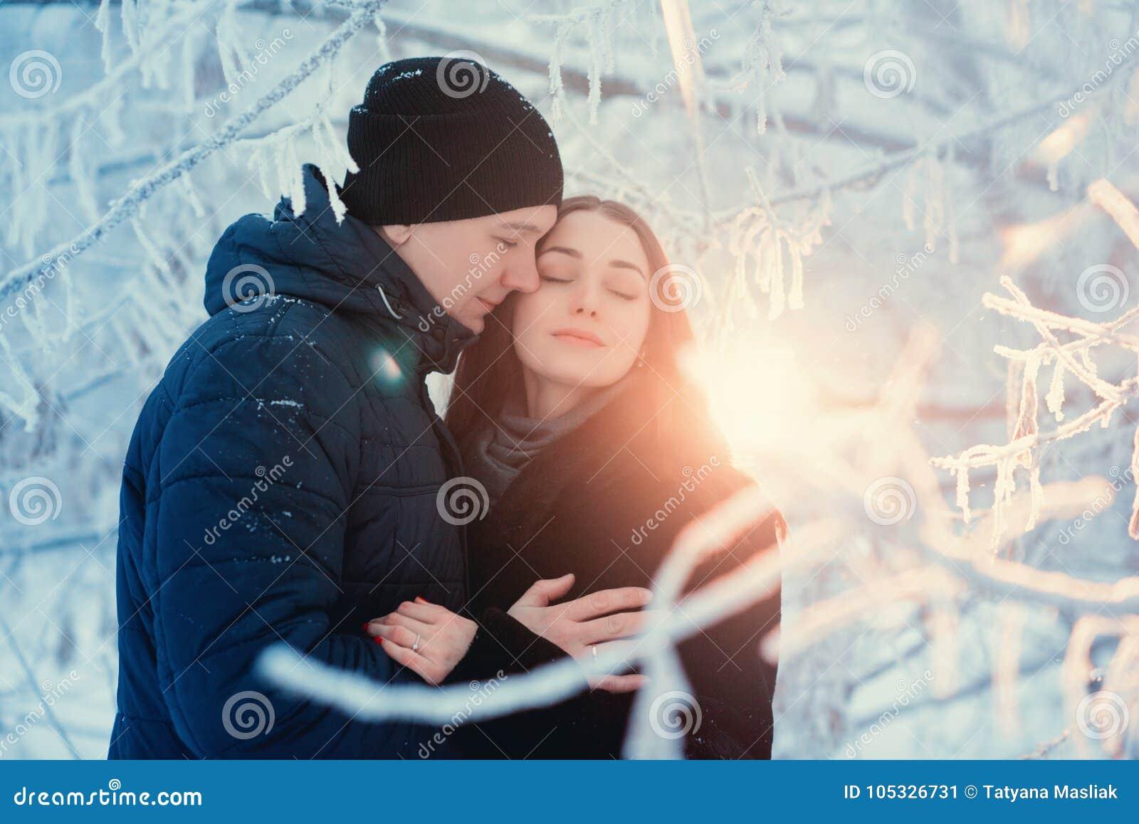 在冬天步行的一对爱恋的夫妇 雪爱情小说,冬天魔术 男人和妇女在冷淡的街道上 人和女孩是休息