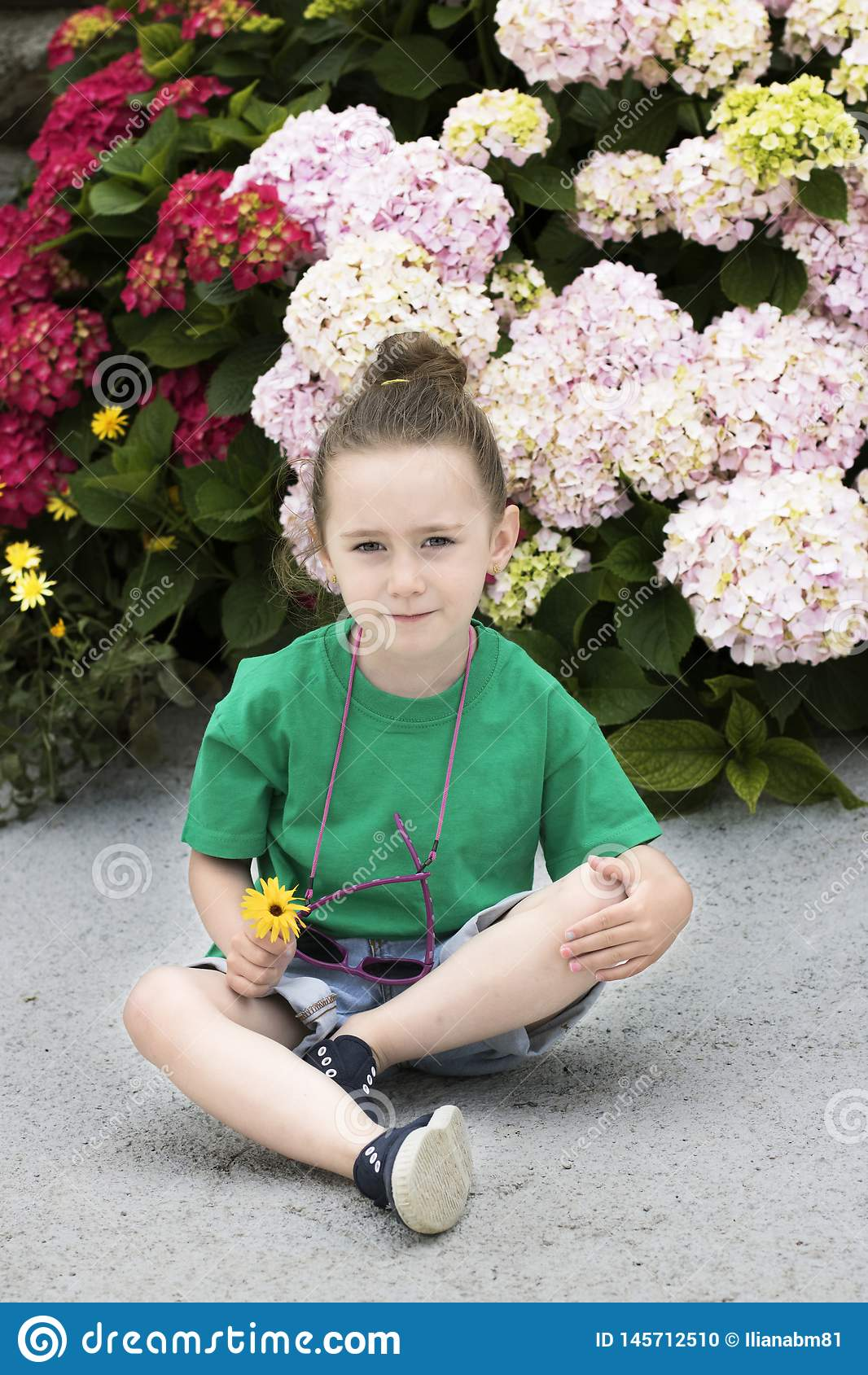 在几开花植物前面的一个四岁的女孩