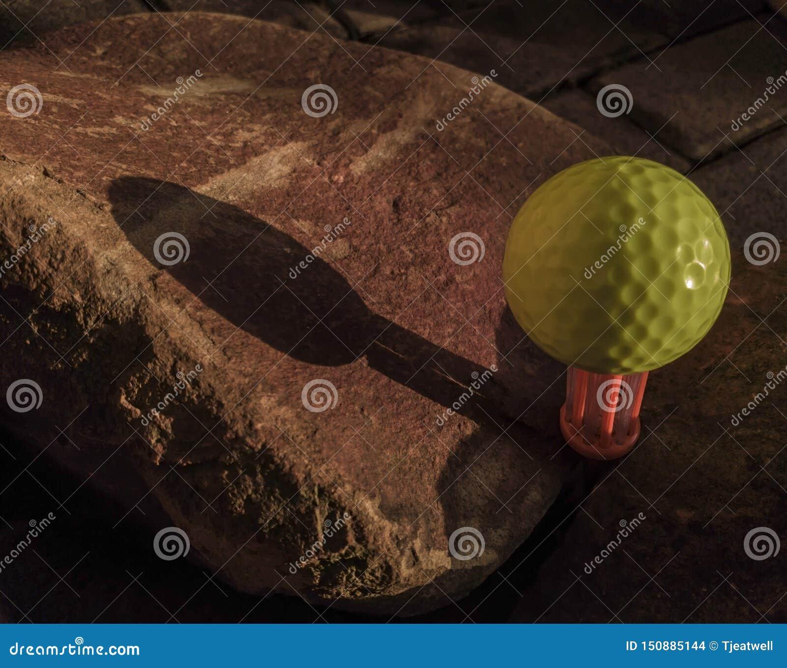 在刷子发球区域的黄色高尔夫球被安置在岩石之间