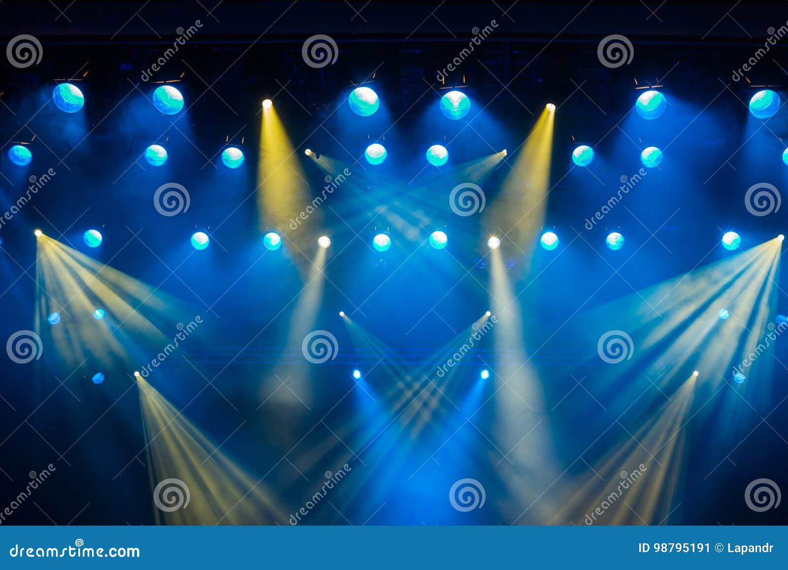 在剧院的阶段的照明设备在表现期间的 从聚光灯的光线通过烟