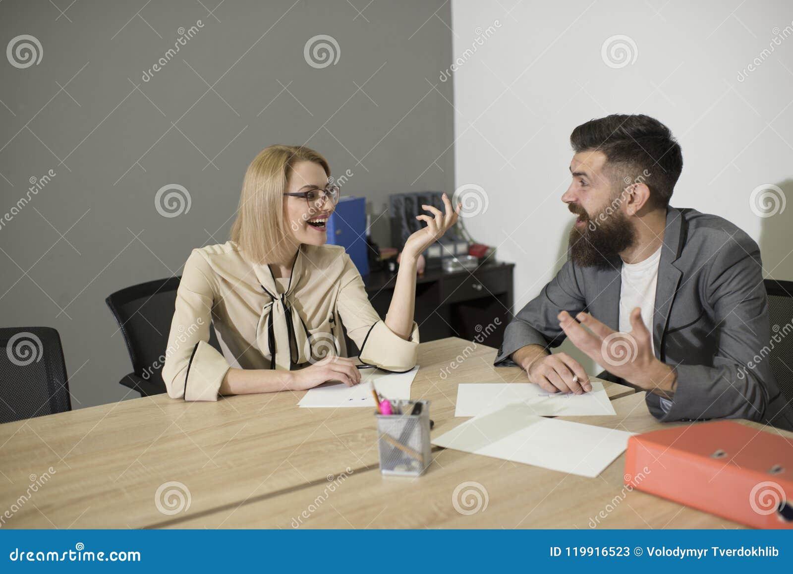 在办公桌的同事愉快的微笑 微笑在业务会议上的同事在办公室、通信和合作