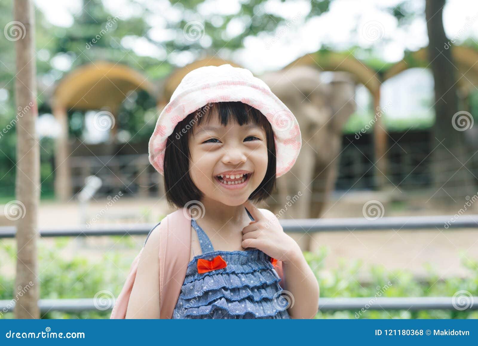 在动物园的逗人喜爱的小女孩观看的动物温暖和晴朗的s的