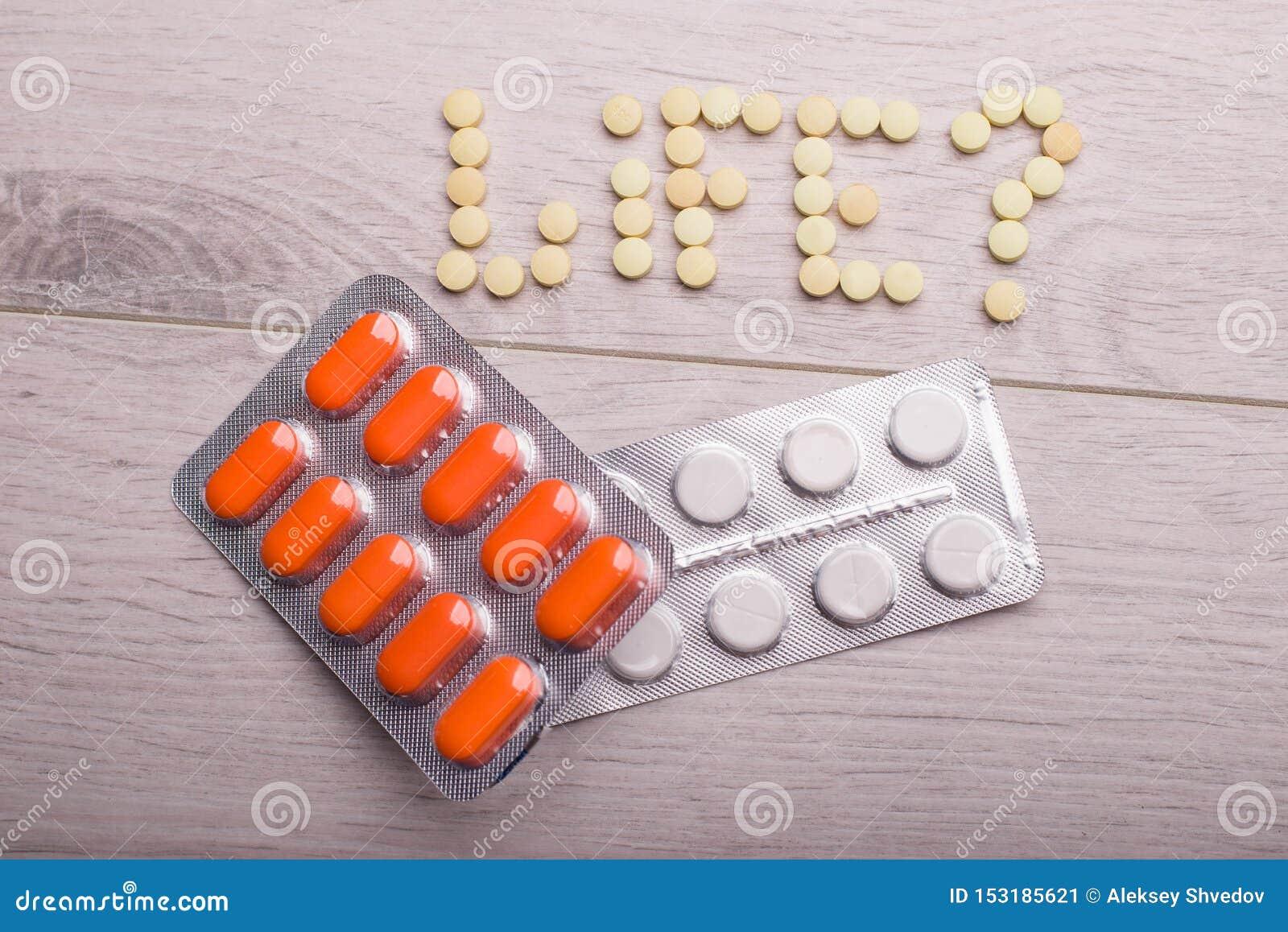 在包裹的橙色和白色药片在桌上