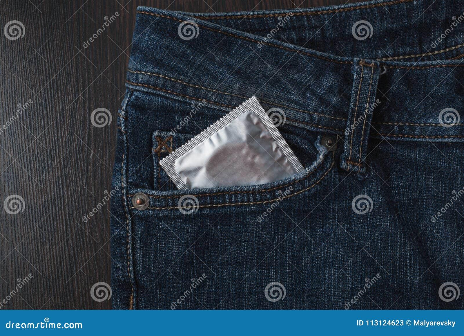 在包裹的避孕套在牛仔裤 概念安全性交 医疗保健医学、避孕和计划生育