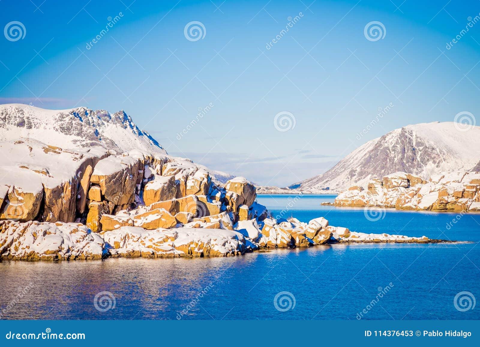 在北极圈的冬天期间被盖的多雪的岩石山室外看法,在华美的蓝天和大海