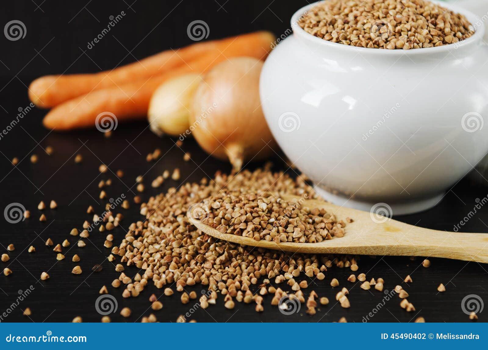 在匙子和碗的未加工的荞麦