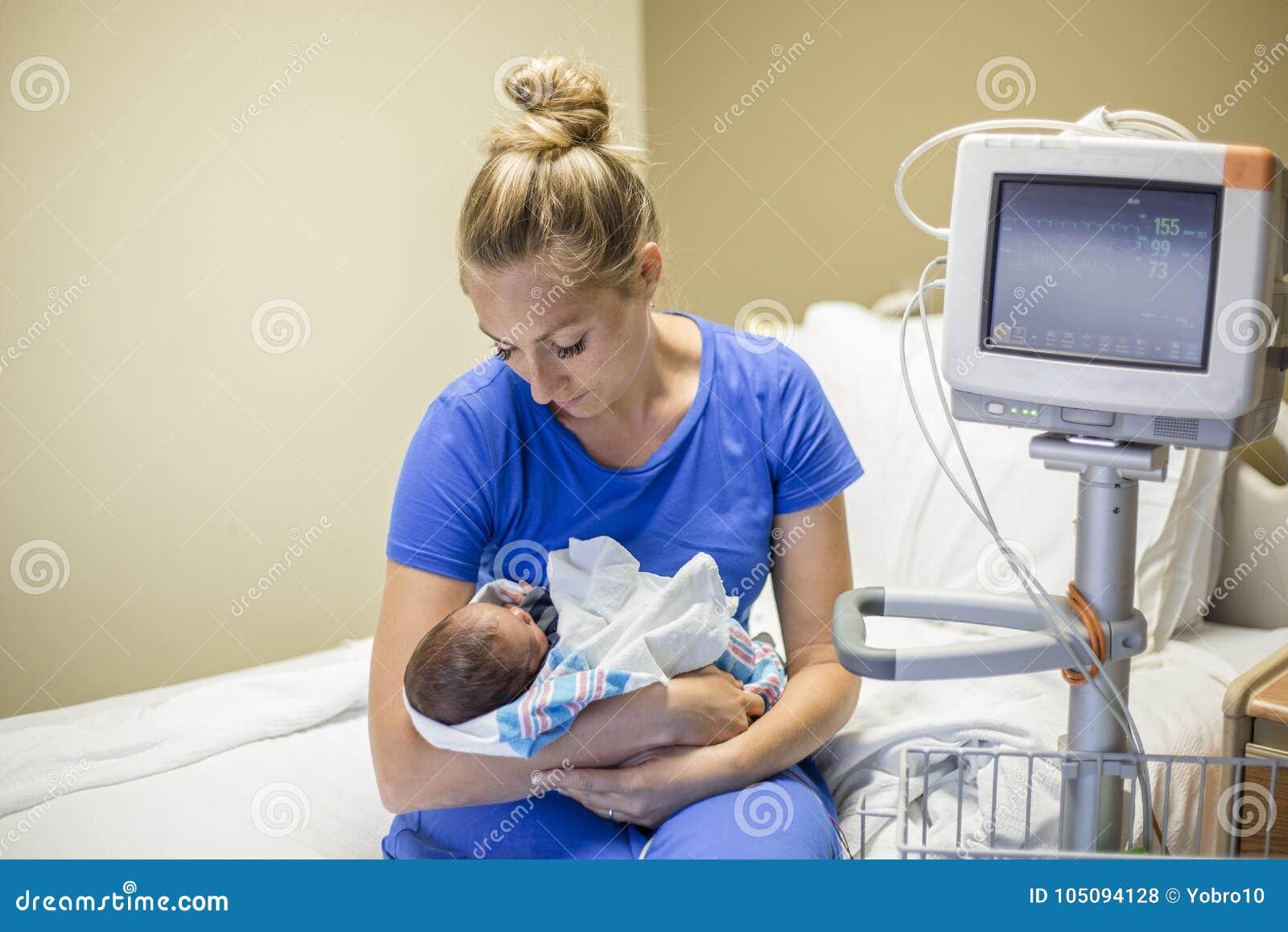 在医院照顾抱着她新出生的早产儿