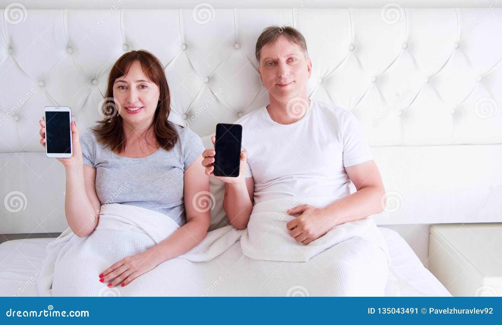 在卧室和拿着手机的家庭