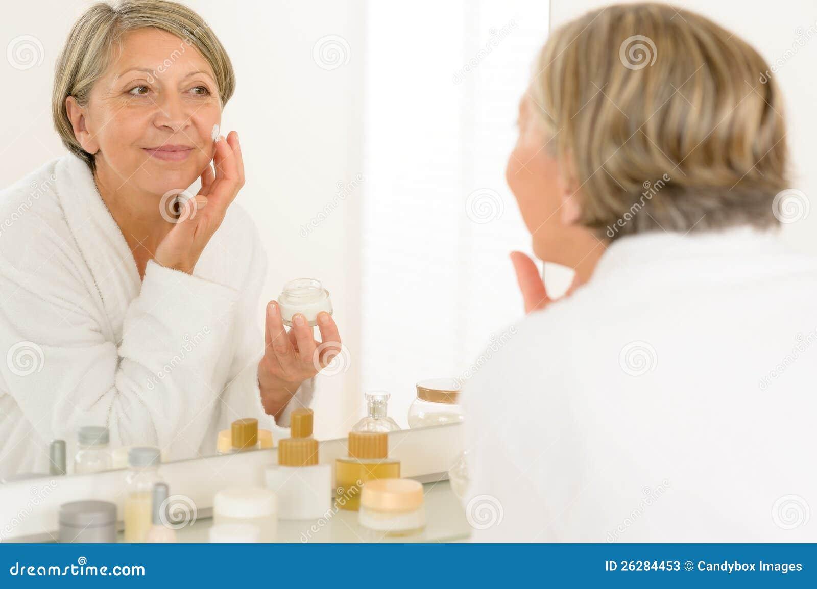 在卫生间镜子的高级妇女反映