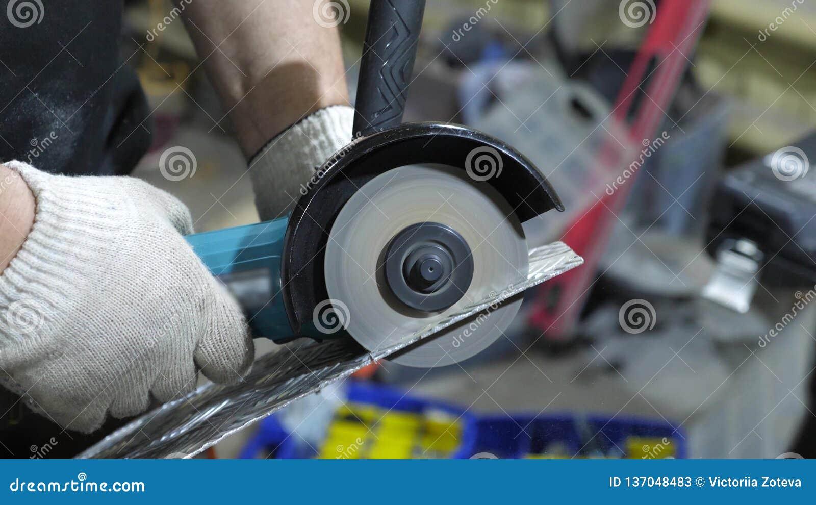 在发光的金属的工作者裁减在白色防护手套研磨机 特写镜头