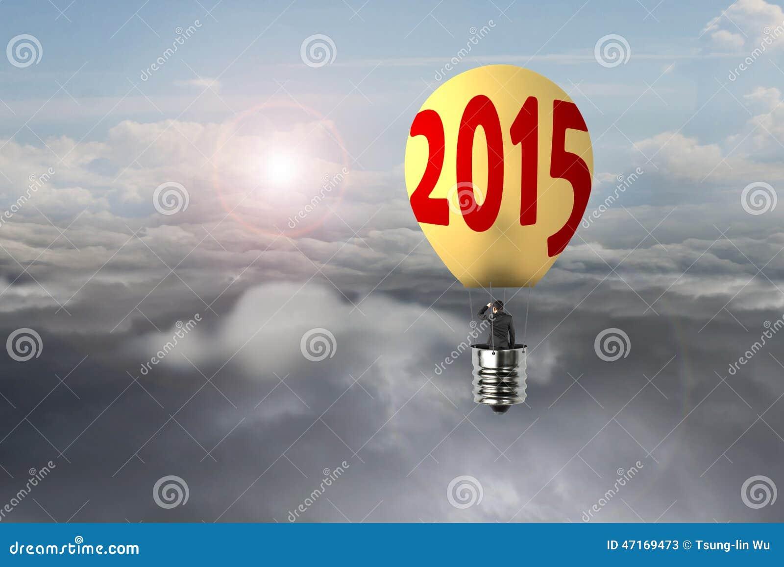 在发光的黄色电灯泡2015热空气气球飞行的商人