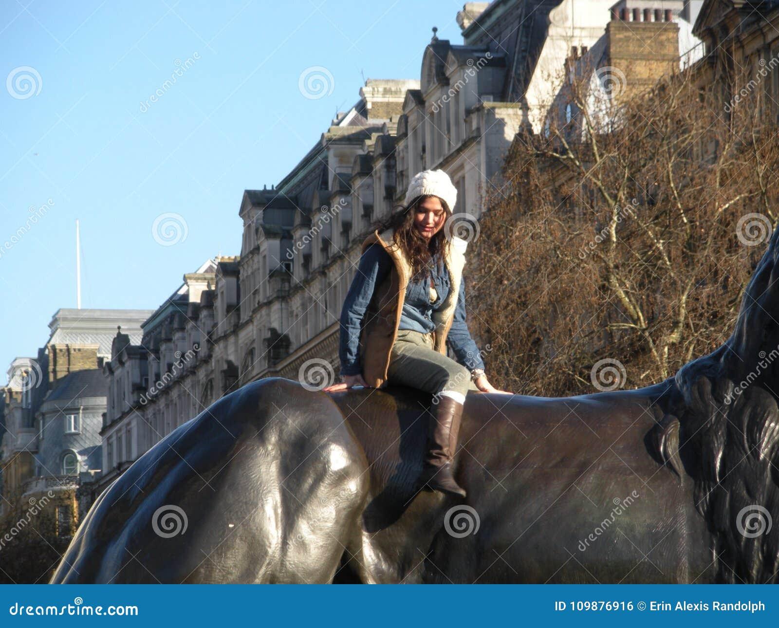 在古铜色狮子,伦敦,英国,英国上面的时兴的少妇姿势