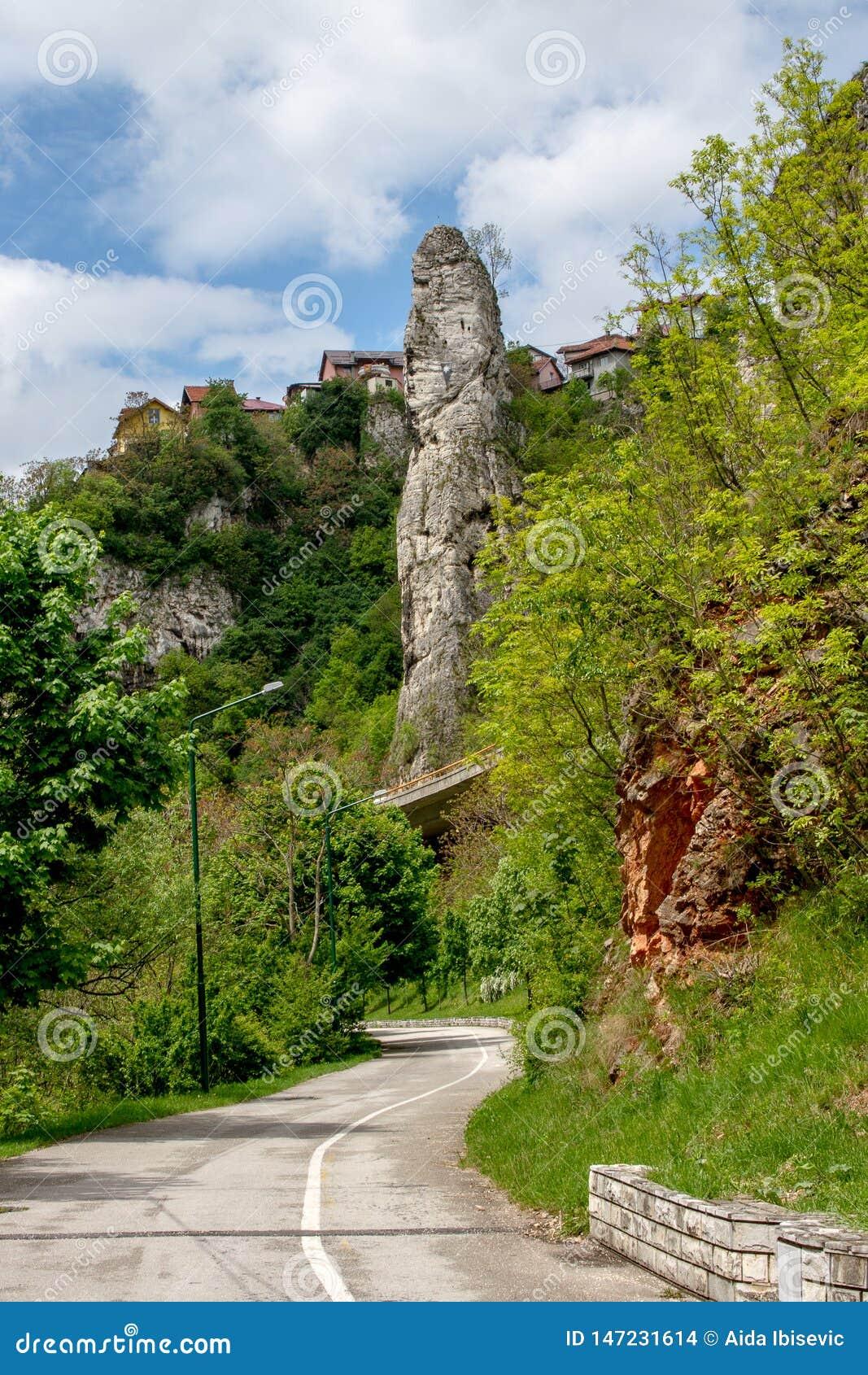 在史诗天空下的山路轮与类似石峭壁的云彩和阴茎