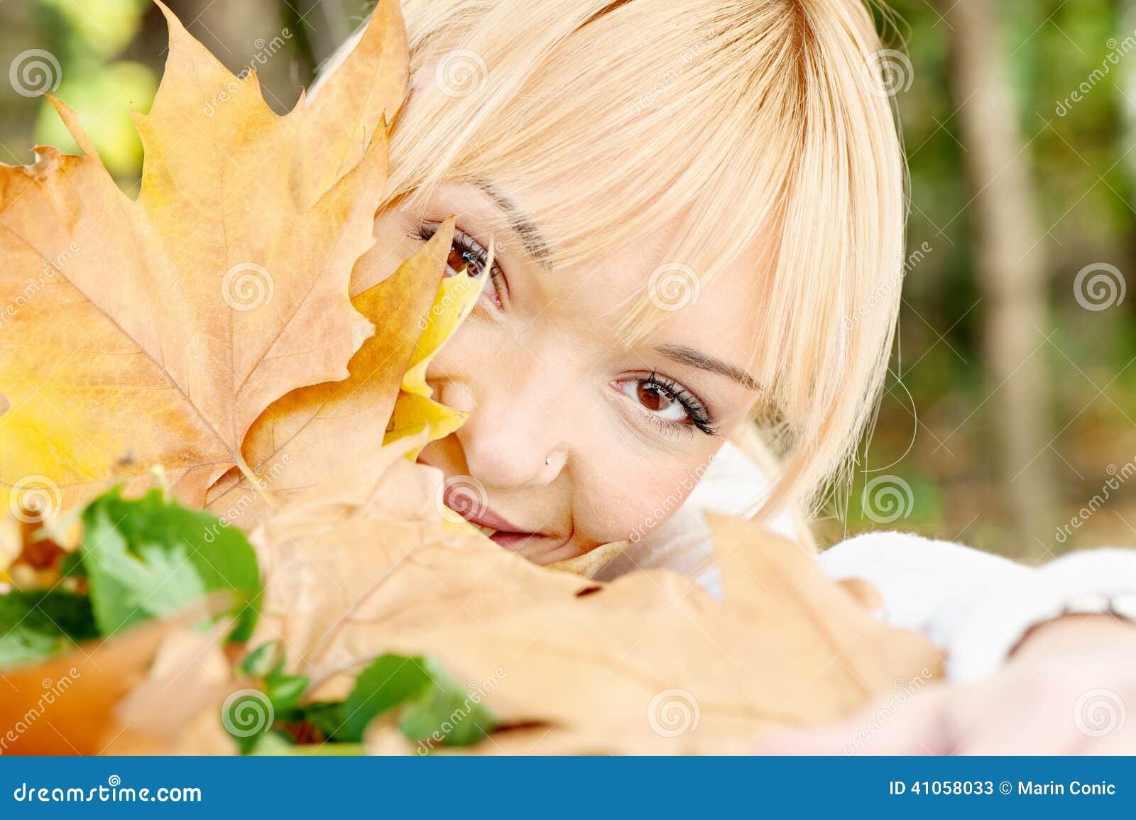 在叶子后的年轻金发碧眼的女人