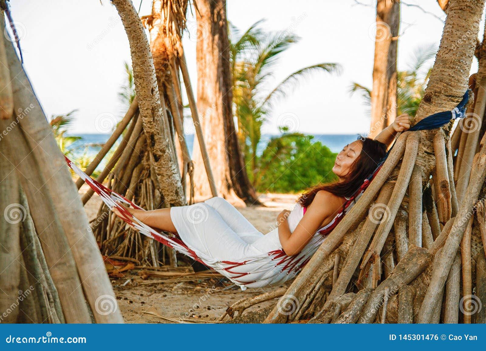 在吊床的画象美好的年轻亚洲妇女幸福微笑休闲在海滩海和海洋附近摇摆有天空蔚蓝白色云彩的